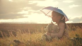 Happy funny little girl with umbrella and toys. Kid playing on the nature outdoors. Child dream concept. stock video footage