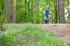 Happy funny little kid boy in colorful raincoat riding his first bike on cold day in forest. Active leisure for children outdoors. Royalty Free Stock Photo