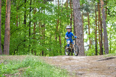 Happy funny little kid boy in colorful raincoat riding his first bike on cold day in forest. Active leisure for children outdoors. Stock Photos