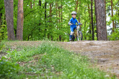Happy funny little kid boy in colorful raincoat riding his first bike on cold day in forest. Active leisure for children outdoors. Royalty Free Stock Image