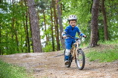Happy funny little kid boy in colorful raincoat riding his first bike on cold day in forest. Active leisure for children outdoors. Royalty Free Stock Photos