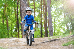 Happy funny little kid boy in colorful raincoat riding his first bike on cold day in forest. Royalty Free Stock Photography