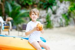 Happy funny little preschool kid boy drinking coconut juice on ocean beach. child playing on family vacations on stock images