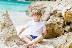 Happy funny little preschool kid boy having fun with building a sand castle on ocean beach. child playing on family. Vacations on tropical island. summer stock photos
