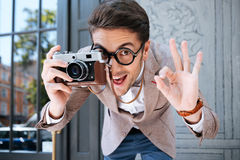Happy funny male photographer in round glasses taking pictures outdoors. Happy funny young male photographer in round glasses showing ok sign and taking pictures royalty free stock photos
