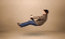 Happy funny man driving a flying car concept Stock Photos
