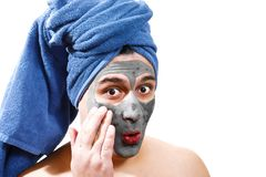 Happy funny man with mask for skin, blue towel on the head, serious man, man is indulging, photo stock photos