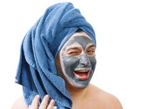 Happy funny man with mask for skin, man likes to make a mask for the skin, blue towel on the head, man winks at the camera, man royalty free stock photography