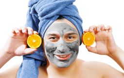 Happy funny man with mask for skin, man likes to make a mask for the skin, man shows orange slices on his face, blue towel on the stock image
