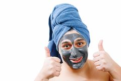 Happy funny man with mask for skin, man likes to make a mask for the skin, man shows class, blue towel on the head, isolated photo royalty free stock photo