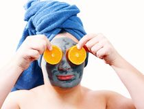 Happy funny man with mask for skin, man likes to make a mask for the skin, man shows orange slices on his face, blue towel on the royalty free stock images