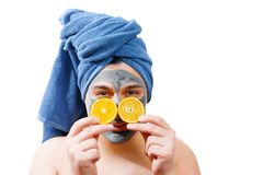 Happy funny man with mask for skin, man likes to make a mask for the skin, man shows orange slices on his face, blue towel on the royalty free stock photo