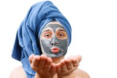 Happy funny man with mask for skin, man sends an air kiss, man likes to make a mask for the skin, blue towel on the head, man stock photos