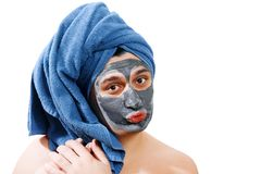 Happy funny man with mask for skin, man sends a kiss, man likes to make a mask for the skin, blue towel on the head, man winks at royalty free stock photos