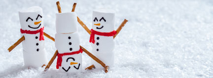 Happy funny marshmallow snowmans on snow royalty free stock photos