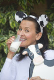 Happy funny mature woman drinkign milk Stock Image