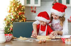 Happy family bake christmas cookies. Happy funny mother and child bake christmas cookies royalty free stock photography