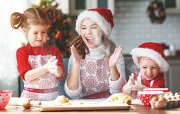 Happy family bake christmas cookies. Happy funny mother and children bake christmas cookies stock image
