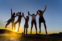 Happy funny people jumping in the sunset. On the beach royalty free stock photography