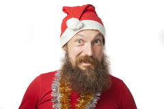Happy funny santa claus with real beard and red hat and shirt making crazy face and smiling, looking and camera Stock Photography