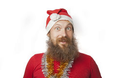 Happy funny santa claus with real beard and red hat and shirt making crazy face and smiling, looking and camera Royalty Free Stock Photos