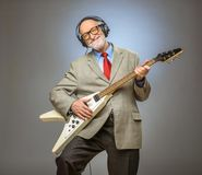 Senior man playing electric guitar. Happy funny senior man playing electric guitar Royalty Free Stock Image