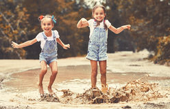 Happy funny sisters twins  child by girl jumping on puddles   and laughing. Happy funny sisters twins  child by girl jumping on puddles in rubber boots and Stock Photos