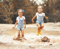 Happy funny sisters twins child girl   jumping on puddles in rub Stock Photo