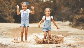 Happy funny sisters twins child girl   jumping on puddles in rub Stock Photos