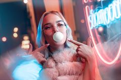 Happy funny teen girl blowing bubble gum illuminated with street neon sign. Happy funny teen hipster girl in fur glasses blowing bubble gum illuminated with stock image