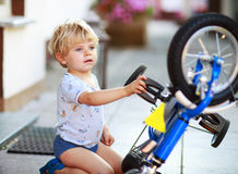 Happy funny toddler boy of two years repairing his first bike Royalty Free Stock Photo
