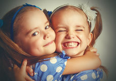 Happy funny twins sisters hugging and laughing Stock Photos