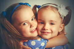 Happy funny twins sisters hugging and laughing Royalty Free Stock Photo