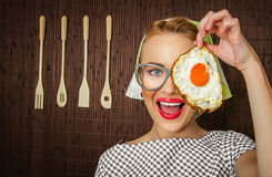 Happy funny woman cook. Holding pan with fried egg - close up Stock Photo