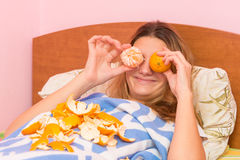 Happy funny woman put tangerines Royalty Free Stock Images