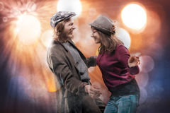 Happy funny young couple dancing over abstract background. Cheerful lovely young men and girl, wearing retro hats and casual clothes, dancing over bright and Royalty Free Stock Photo
