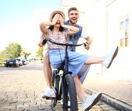 Happy funny young couple riding on bicycle. Love, relationship, romance concept royalty free stock photo