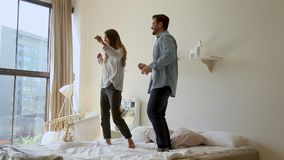 Happy funny young family couple dancing jumping on bed mattress