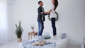 Happy funny young family couple jumping on bed mattress, active carefree husband and wife having fun laughing enjoying
