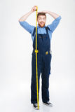 Happy funny young man measuring his body height using tape. Happy funny young man in overall measuring his body height using tape Stock Images