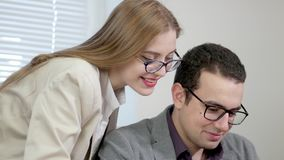 Happy funny young people - men and woman - in office playing with computer. Laughing at something on the screen. stock footage