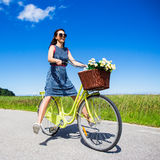 Happy funny young woman riding on bicycle with raised legs Royalty Free Stock Photos