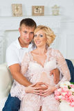 Happy future father with beautiful cute pregnant woman sitting on sofa with flowers. Stock Image