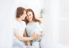 Happy future parents, dad and a pregnant mother in anticipation. Of baby at home royalty free stock image