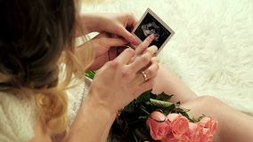 Happy future parents looking at pregnancy ultrasound photo stock footage