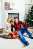 Happy future parents are sitting on the carpet in the room decorated to Christmas holidays. Pregnant woman is observing royalty free stock images