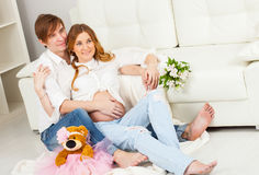 Happy future parents sitting together near the white sofa Royalty Free Stock Photo