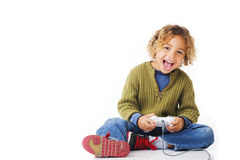 Happy Gamer. Curly blonde 5 year old boy sitting smileing with game controls on white background Stock Photography