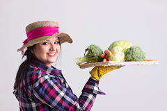 Happy Garden Woman with Tray of Vegetables. Happy Long Hair Reliable Woman with Leghorn and Garden Gloves is Holding a Wicker Tray with Vegetables   Isolated on Stock Image