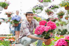 Happy gardener holding flower pot with colleague standing in background at greenhouse Royalty Free Stock Photos